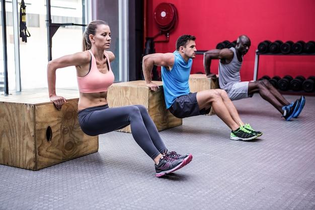 Três jovens bodybuilders fazendo exercícios Foto Premium