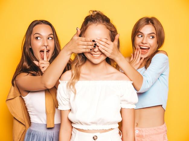 Três jovens bonitas garotas hipster sorridentes em roupas da moda no verão. mulheres despreocupadas sexy posando perto da parede amarela. modelos surpreendendo seu amigo. eles cobrem os olhos dela e abraçando por trás Foto gratuita