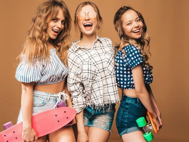 Três jovens elegantes sexy sorridentes meninas bonitas com skates centavo coloridos. mulheres em roupas de camisa quadriculada verão posando em óculos de sol. modelos positivos se divertindo Foto gratuita
