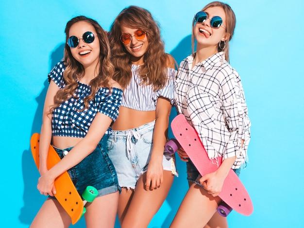 Três jovens elegantes sorridentes meninas bonitas com skates centavo colorido. mulheres em roupas de verão, posando em óculos de sol. modelos positivos se divertindo Foto gratuita