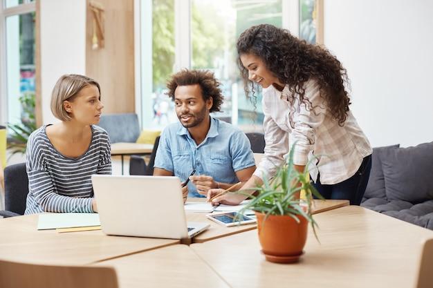 Três jovens empreendedores em perspectiva, sentado na biblioteca, discutindo planos de negócios e lucros da empresa, fazendo pesquisas de negócios com laptop, olhando através de informações no tablet. Foto gratuita