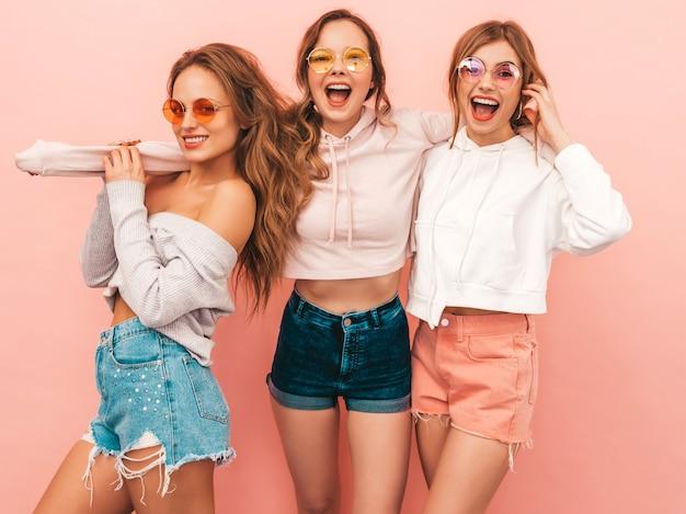 Três jovens lindas meninas sorridentes em roupas da moda no verão. mulheres sexy despreocupadas posando. modelos positivos se divertindo Foto gratuita