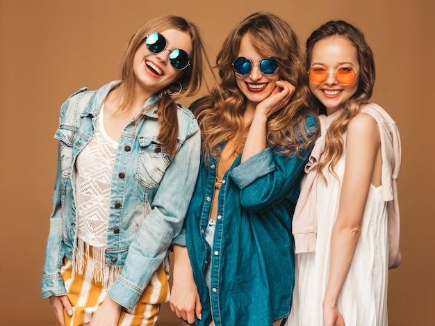 Três jovens lindas meninas sorridentes em roupas de jeans casual de verão na moda. mulheres sexy despreocupadas posando. modelos positivos em óculos de sol Foto gratuita