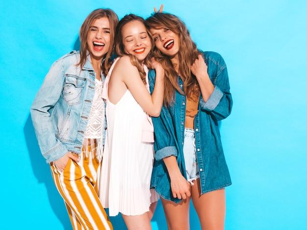Três jovens lindas meninas sorridentes em roupas de jeans casual de verão na moda. mulheres sexy despreocupadas posando. modelos positivos Foto gratuita
