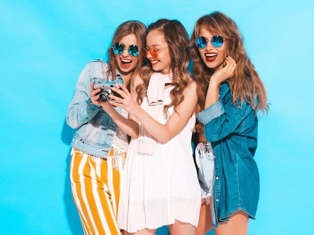Três jovens lindas meninas sorridentes em vestidos casuais de verão na moda e em óculos de sol. mulheres sexy despreocupadas posando. tirando fotos na câmera retro Foto gratuita