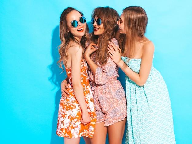 Três jovens lindas meninas sorridentes em vestidos casuais de verão na moda e em óculos de sol. mulheres sexy despreocupadas posando. Foto gratuita