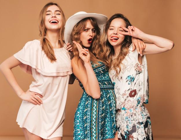 Três jovens lindas meninas sorridentes em vestidos casuais de verão na moda. mulheres sexy despreocupadas posando. Foto gratuita