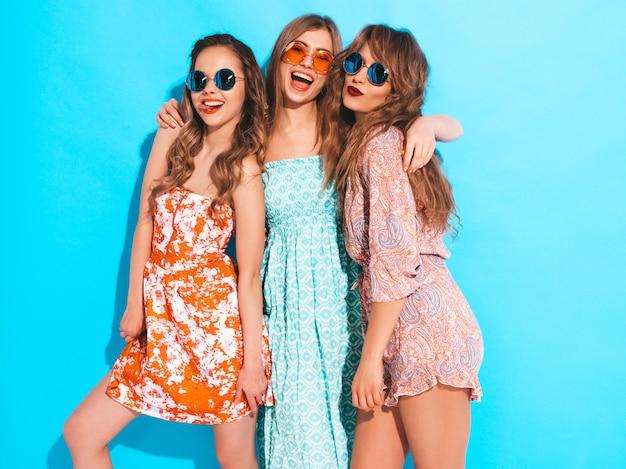 Três jovens lindas meninas sorridentes em vestidos coloridos na moda verão. mulheres despreocupadas sexy em óculos de sol. Foto gratuita