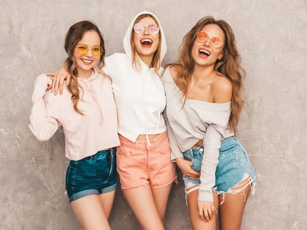 Três jovens lindas meninas sorridentes no verão na moda esporte roupas. mulheres sexy despreocupadas posando. modelos positivos em óculos de sol redondos se divertindo. abraçando Foto gratuita