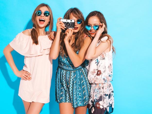 Três jovens lindas meninas sorridentes no verão na moda vestidos coloridos e óculos de sol. mulheres sexy despreocupadas posando. tirando fotos na câmera retro Foto gratuita