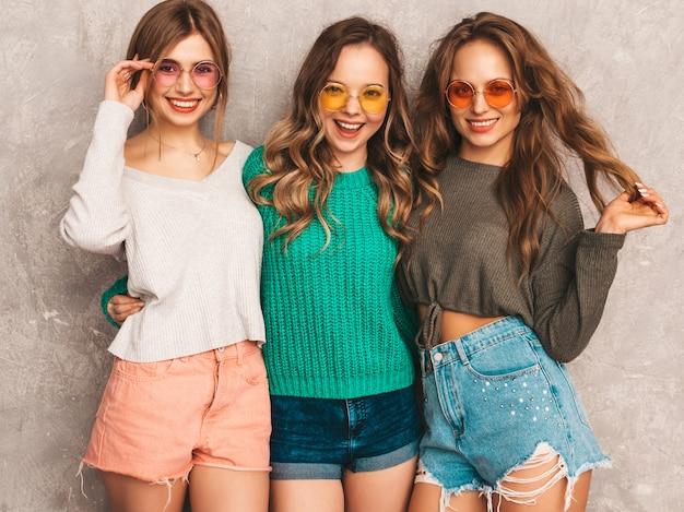Três jovens lindas sorrindo lindas garotas em roupas da moda no verão. mulheres sexy despreocupadas posando. modelos positivos se divertindo em óculos de sol redondos Foto gratuita