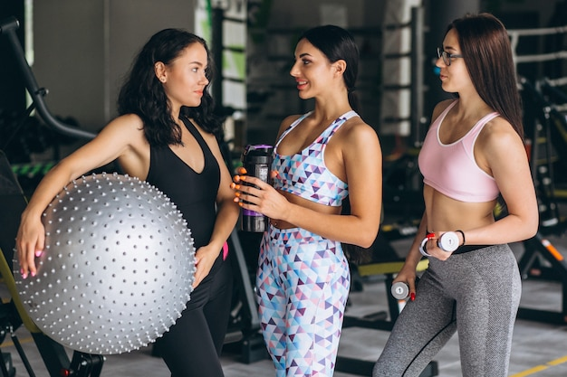 Três jovens mulheres treinando na academia Foto gratuita