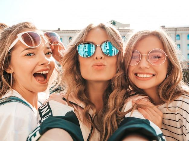 Três jovens sorrindo hipster mulheres em roupas de verão. meninas tirando fotos de auto-retrato de selfie em smartphone. modelos posando na rua. feminino mostrando emoções de rosto positivo em óculos de sol Foto gratuita