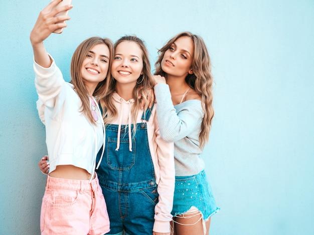 Três jovens sorrindo hipster mulheres em roupas de verão. meninas tirando fotos de auto-retrato de selfie em smartphone. modelos posando na rua perto da parede. feminino mostrando emoções de rosto positivo Foto gratuita