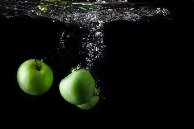 Três maçãs verdes espirrando na água em fundo preto. copie o espaço Foto Premium