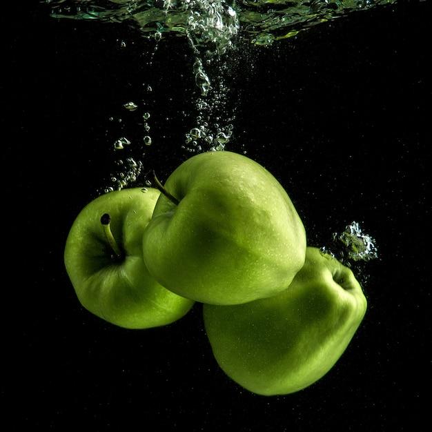 Três maçãs verdes frescas na água Foto gratuita