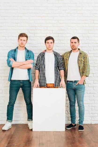 Três, macho, amigos, com, branca, em branco, painél publicitário, olhando câmera Foto gratuita