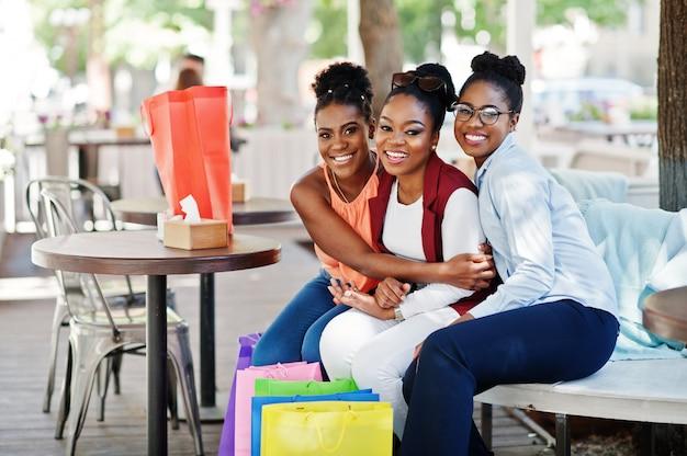 Três meninas afro-americanos ocasionais com sacos de compras coloridos que andam ao ar livre. mulher negra elegante às compras. Foto Premium