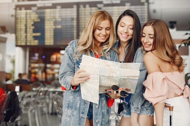 Três meninas bonitas em pé no aeroporto Foto gratuita