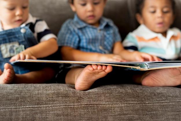 Três, menininhos, lendo um livro, ligado, um, sofá Foto Premium