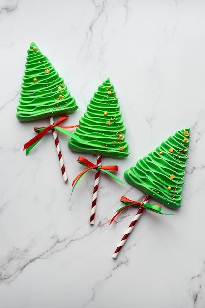 Três merengues em um fundo de mármore. doces para a mesa do ano novo. Foto Premium