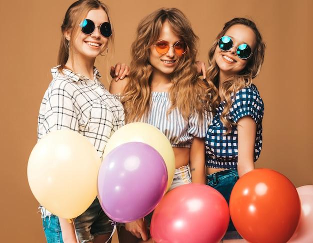 Três mulheres bonitas sorridentes em roupas de verão camisa quadriculada e óculos de sol. meninas posando. modelos com balões coloridos. se divertindo, pronto para comemorar aniversário Foto gratuita