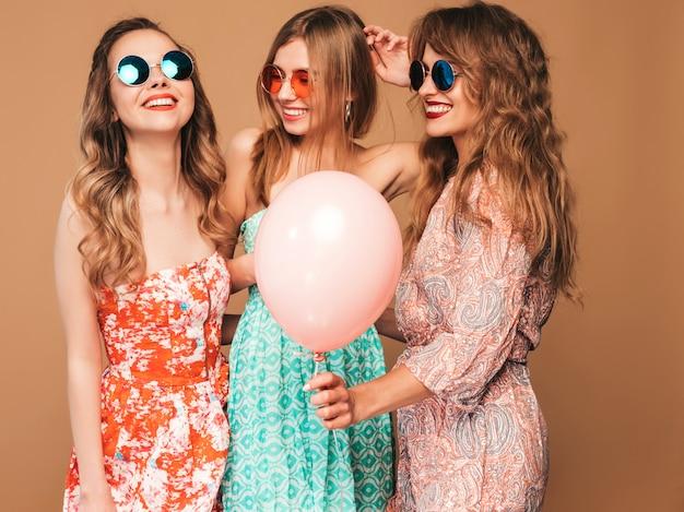 Três mulheres bonitas sorridentes em roupas de verão camisa quadriculada. meninas posando. modelos com balões coloridos em óculos de sol. se divertindo, pronto para comemorar aniversário ou festa natalícia Foto gratuita