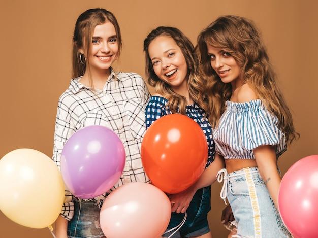 Três mulheres bonitas sorridentes em roupas de verão camisa quadriculada. meninas posando. modelos com balões coloridos. se divertindo, pronto para a festa de aniversário de comemoração Foto gratuita
