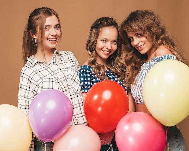 Três mulheres bonitas sorridentes em roupas de verão camisa quadriculada. meninas posando. modelos com balões coloridos. se divertindo, pronto para comemorar aniversário Foto gratuita