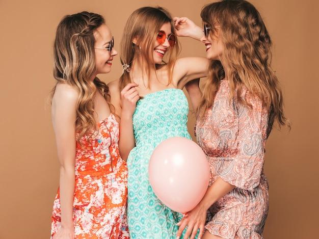 Três mulheres bonitas sorridentes em vestidos de verão. meninas posando. modelos com balões coloridos. se divertindo, pronto para comemorar aniversário ou festa natalícia Foto gratuita