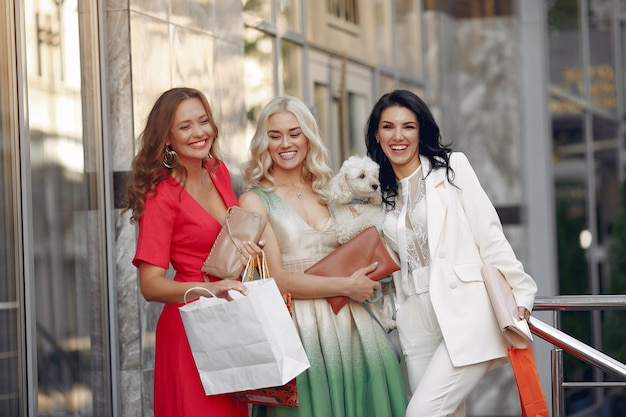 Três mulheres elegantes com sacolas de compras em uma cidade Foto gratuita
