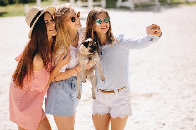 Três mulheres, praia, com, cachorro pequeno Foto gratuita