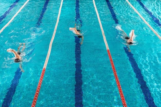 Três nadadores masculinos correndo um contra o outro Foto gratuita
