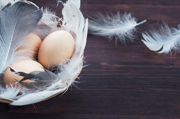 Três ovos de galinha em uma cesta com penas Foto Premium
