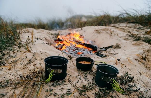 Três panelas com comida na areia com fogo Foto Premium