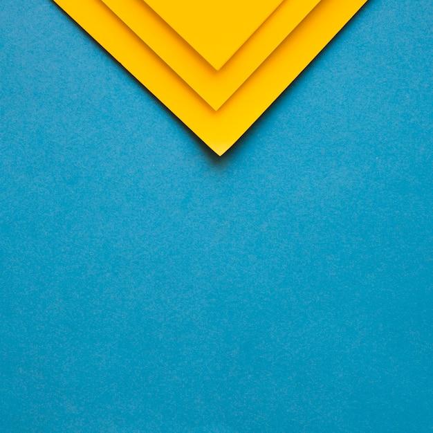 Três papéis de papelão amarelo no topo do pano de fundo azul Foto gratuita