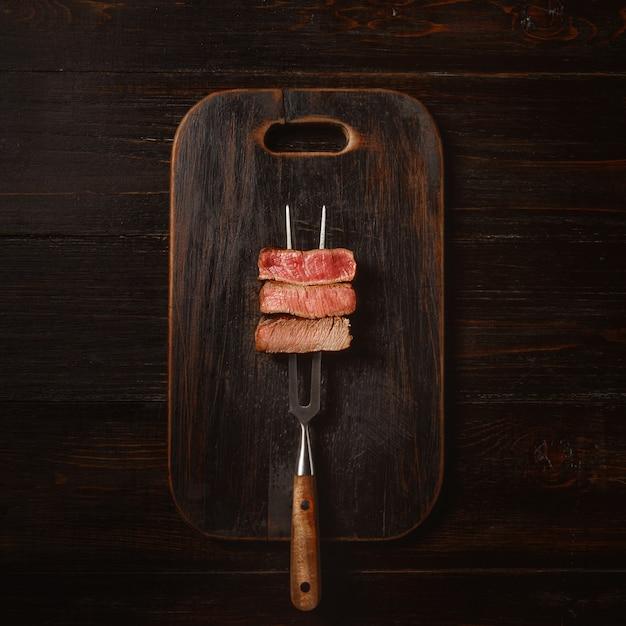 Três pedaços de carne em um garfo para carne. três tipos de carne assada, rara, média e bem passada. Foto Premium