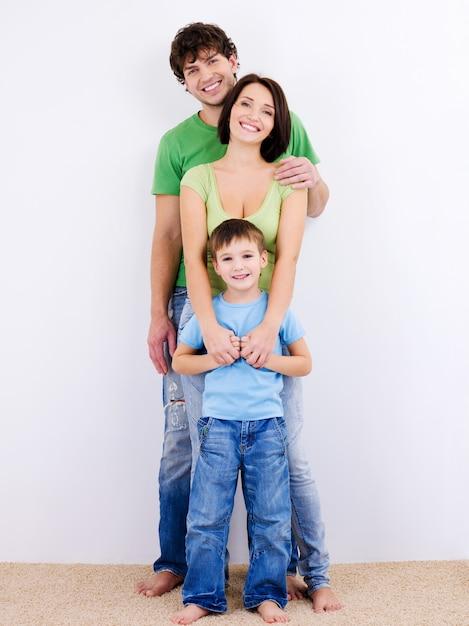 Três pessoas da jovem família feliz e sorridente Foto gratuita