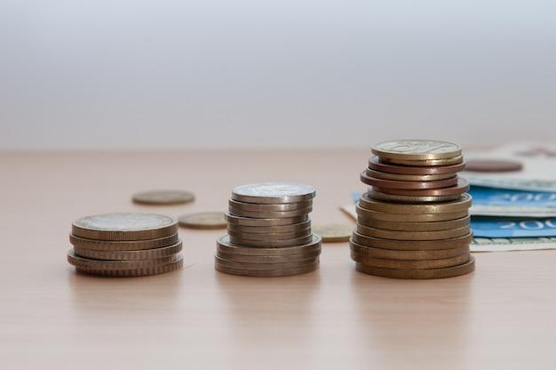 Três pilhas de moedas e contas mentem sobre a mesa. Foto Premium