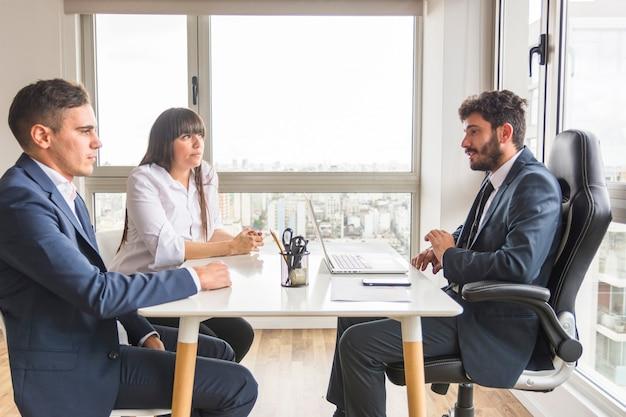 Três profissionais de negócios trabalhando juntos no escritório Foto gratuita