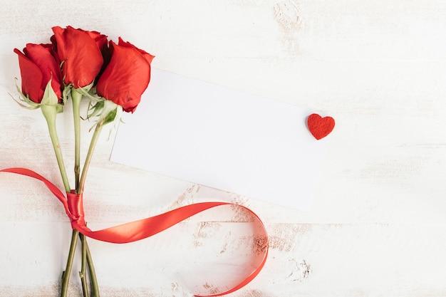 Três rosas e papel branco para mensagem Foto gratuita