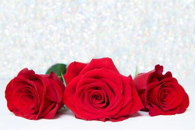 Três rosas vermelhas com fundo boke Foto Premium
