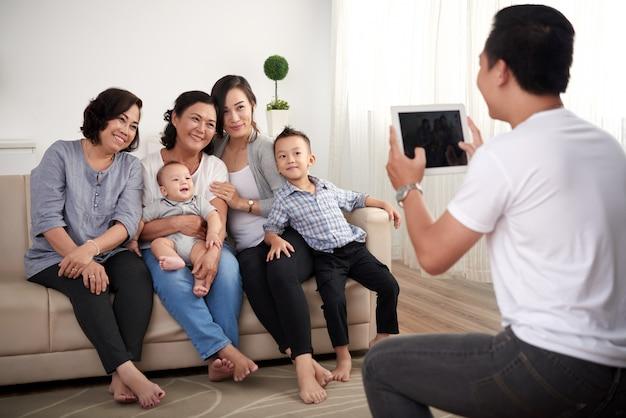Três senhoras asiáticas com menino e bebê sentado no sofá e homem tirando fotos no tablet Foto gratuita