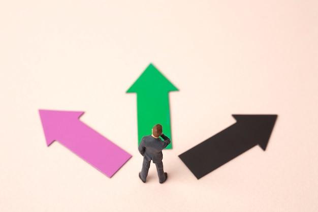 Três setas de direção com homem de negócios em miniatura Foto Premium