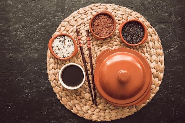 Três tigelas de grãos de arroz cru com molho de soja; pauzinhos no placemat Foto gratuita