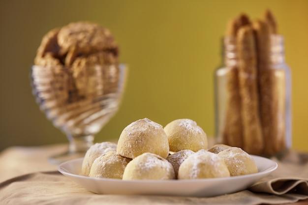 Três tipos de biscoitos em tons de bege em um guardanapo em um prato e em uma jarra. o conceito de estilo rústico Foto Premium