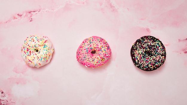 Três tipos de branco; rosquinhas de chocolate e rosa com granulado contra fundo rosa Foto gratuita