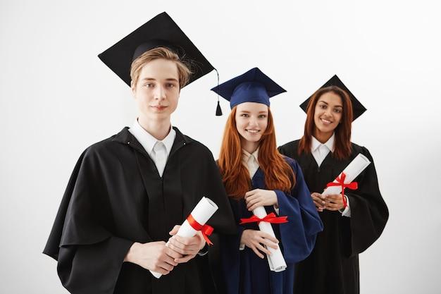 Três universitários internacionais felizes que sorriem alegrando-se guardando diplomas. futuros advogados ou engenheiros. Foto gratuita