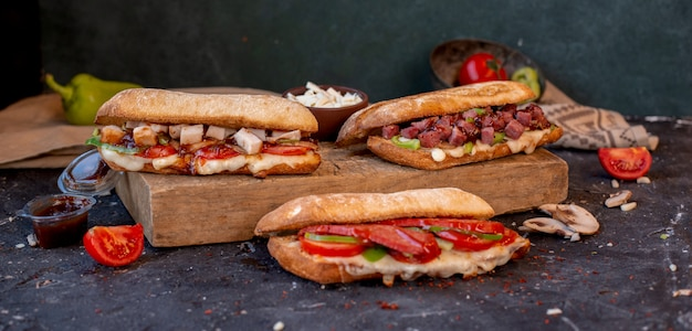 Três vários sanduíches de baguete com alimentos misturados em uma mesa de pedra Foto gratuita