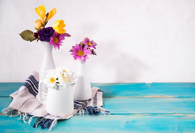 Três vasos com flores brilhantes na mesa Foto gratuita